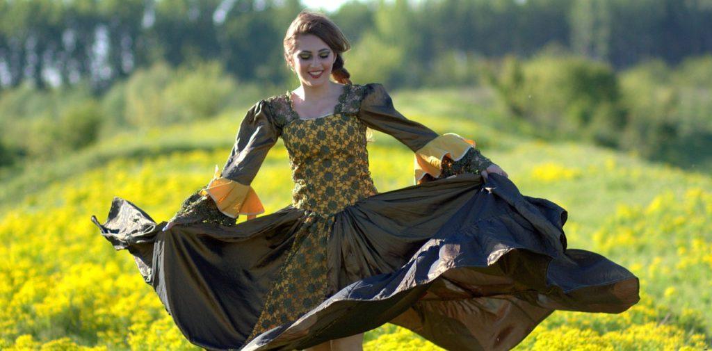 Kobieta tańczy na łące pełnej kwiatów